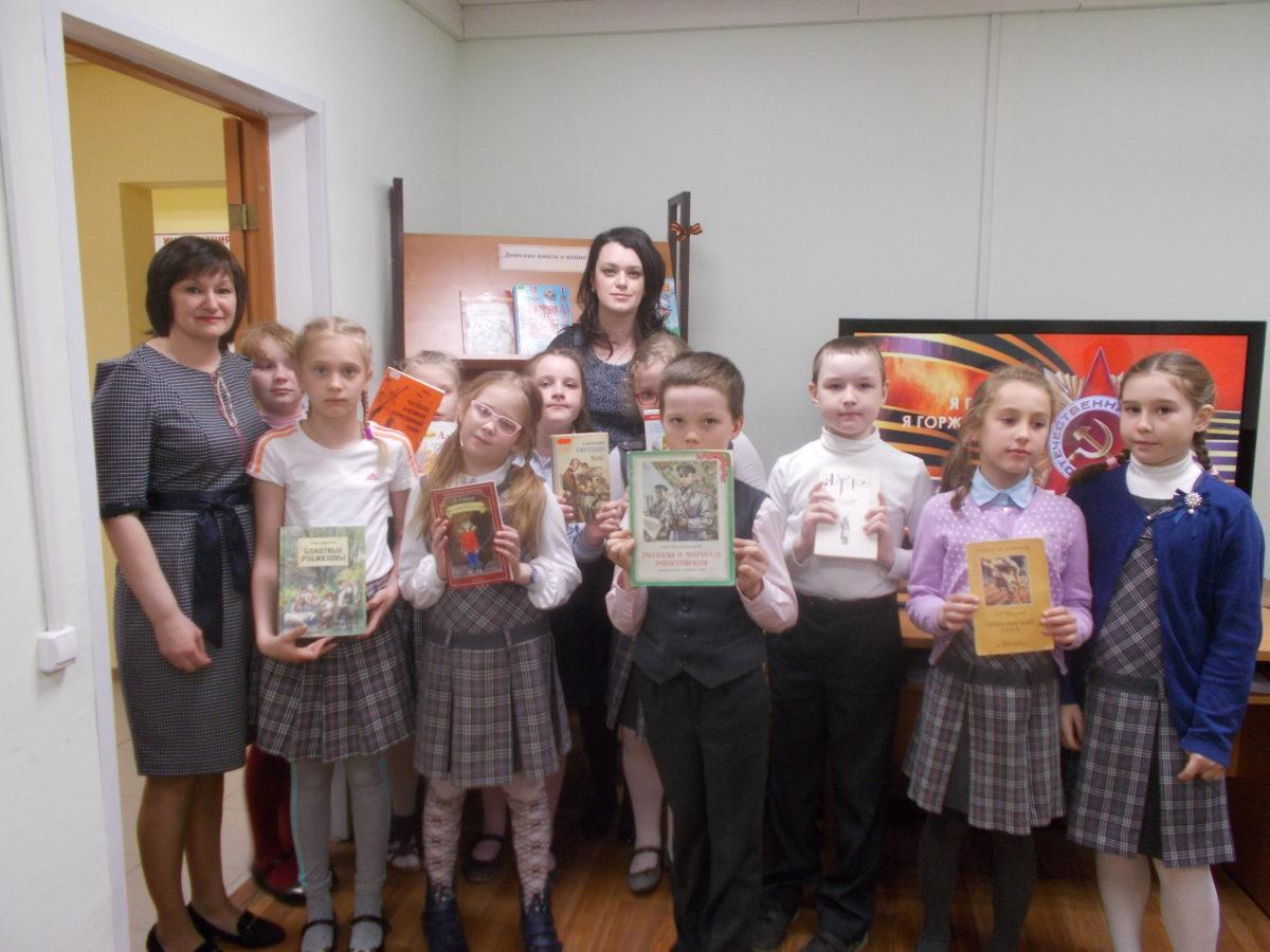 Дети стоят на фоне стелажа. держа в руках книги о Великой Отечественной Войне