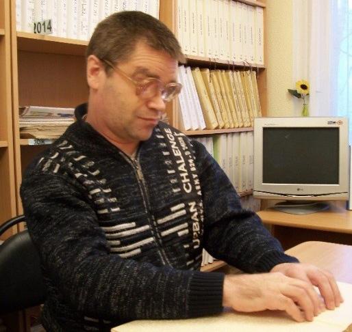 Читатель читает книгу рельефно-точечного шрифта